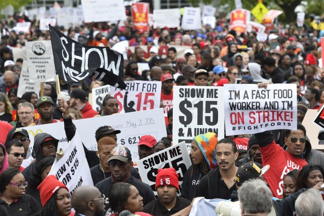 Demonstrators march on McDonald's corporate headquarters demanding a wage increase to $15 per hour in 2015. File Photo by Brian Kersey/UPI