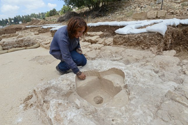 Archeologist Annette Nagar from the Israeli Antiquities Authority examines a child baptismal in an ancient Byzantine church dating back 1,500 years in Beit Nakofa, near Jerusalem. According to archeologists, the church was used by pilgrims on the ancient road to Jerusalem from the coastal plain. Photo by Debbie Hill/UPI