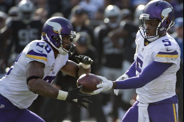 Minnesota Vikings QB Teddy Bridgewater (5) hands off to RB Adrian Peterson. Photo by Terry Schmitt/UPI