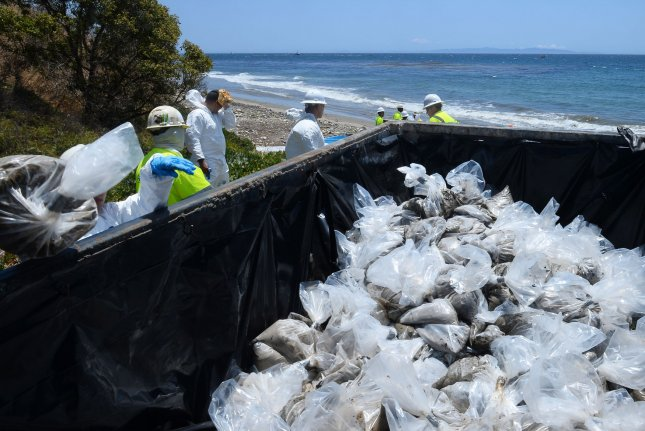 Workers form an assembly line to place bags of sand contaminated by oil in a dumpster for disposal along Refugio Beach. A unified command center established for the spill said the worst-case estimate is that 2,500 barrels of oil was released from a pipeline operated by Plains All American. Photo by Jim Ruymen/UPI