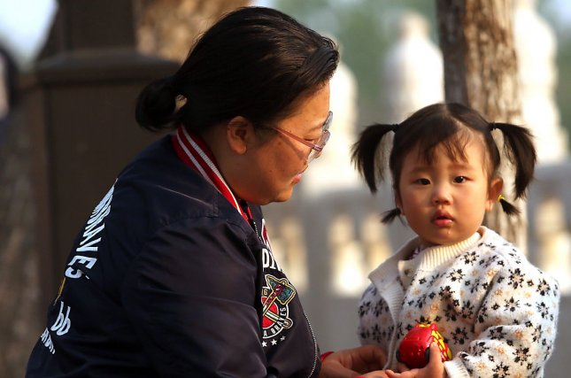 A mother walks through a park with her daughter in Beijing in April. On Monday, China said it would allow parents to have three children, doing away with its two-child policy in place since 2015. Photo by Stephen Shaver/UPI