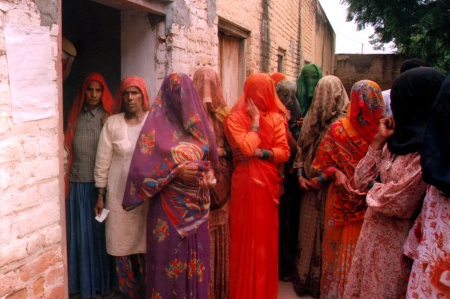 Indian women with veiled faces wait for their turns to cast ballots at a polling station in a rural area in Bhiwani district of India in 1999. (UPI/stringer)