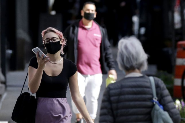 Masked pedestrians are seen Wednesday walking along Madison Avenue in New York City. Photo by John Angelillo/UPI