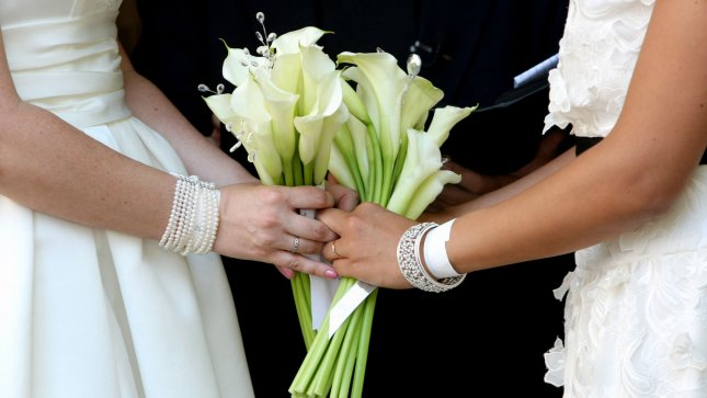 Jen (L) and Rose Nagle-Yndigoyed hold hands as they exchange wedding vows in Central Park on July 30, 2011 in New York City. Nearly a week after New York State legalized same-sex marriages gay couples have been marrying throughout the state. UPI /Monika Graff