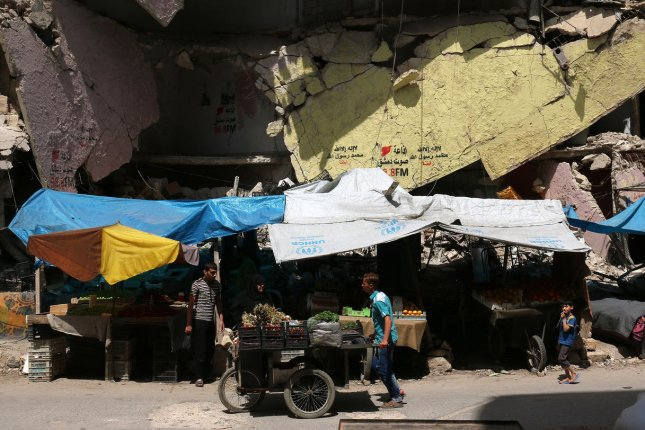 Vendors sell fruits and vegetables in the rebel-held Bustan al-Qasr district in eastern Aleppo, Syria on May 21, 2016. Airstrikes have hit rebel-held parts city Sunday. Photo by Ameer Alhalbi/ UPI