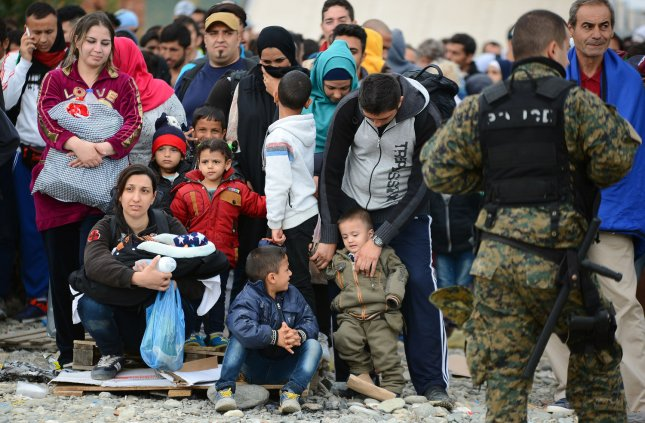 Migrants and refugees wait to cross the border into northern Greece on Sept. 8. The Human Rights Watch advocacy group said Thursday a group of armed attackers are intercepting boats full of migrants in the Aegean Sea and forcing them to go back. Photo by Borce Popovski/UPI