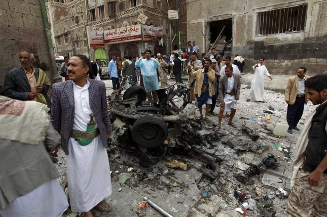 Houthi fighters inspect the wreckage of a car at the site of an attack near of Qubbat al-Mahdi Mosque in Sanaa, Yemen, last June. File Photo by Mohammad Abdullah/UPI