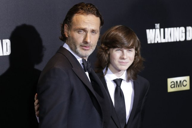 Chandler Riggs (R), pictured with Andrew Lincoln, debuted a new haircut following The Walking Dead midseason finale. File Photo by John Angelillo/UPI