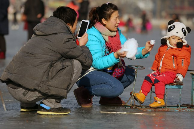 Chinese families and students visit a frozen lake to skate, ski at a popular tourist area in Beijing on Feb. 6. China's relaxation of its one-child policy has led to more mothers giving a second child their maiden name. File Photo by Stephen Shaver/UPI