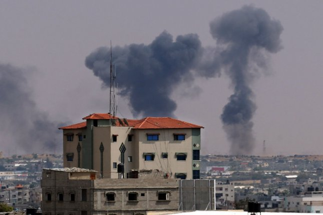Smoke billows in the background following an Israeli air strike on the Palestinian enclave Rafah in the southern Gaza Strip on Tuesday. The Israeli military launched a series of air strikes on Palestinian positions in Gaza after a barrage of rocket fire from the Strip. Photo by Ismael Mohamad/UPI