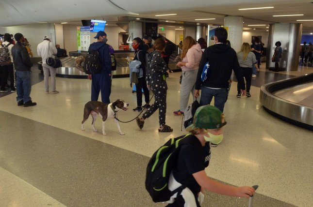 Travelers -- and their dog -- gather their luggage at Los Angeles International Airport on November 25. On Wednesday, the Trump administration finalized rules allowing airlines to restrict service animals only to dogs. Photo by Jim Ruymen/UPI