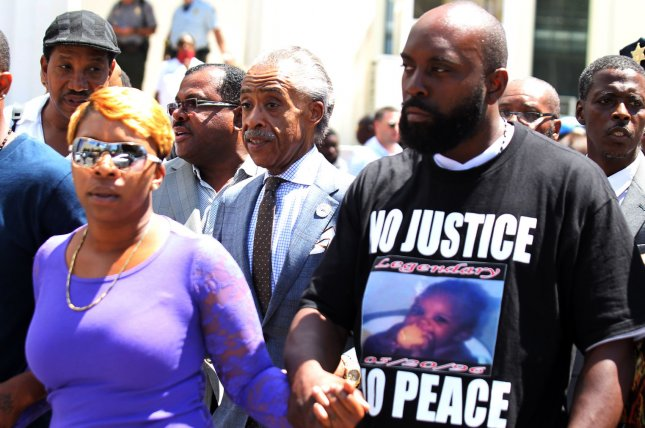 Rev. Al Sharpton walks with Michael Brown Sr. and Lesley McSpadden as he prepares to deliver remarks to reporters on the steps of the Old Courthouse in St. Louis on August 12, 2014. Sharpton was on hand to meet with the family of and give his thoughts on the police killing of unarmed teen Michael Brown on August 9, 2014. UPI/Bill Greenblatt