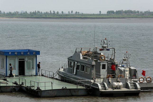 Chinese military patrol boats are stationed on the Yalu River across from North Korea (background) in Dandong, China's largest border city with North Korea. After Chinese authorities have increased their inspection of cargo going in and out of North Korea, Pyongyang's diplomats are using a circuitous route into Mongolia to send luxury goods into the country. File Photo by Stephen Shaver/UPI