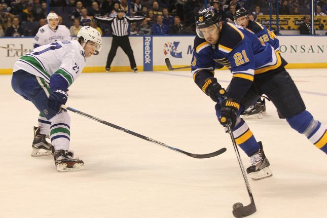 St. Louis Blues Patrik Berglund tries to work the puck past Vancouver Canucks Ben Hutton in the first period at the Scottrade Center in St. Louis on March 25, 2016. Photo by Bill Greenblatt/UPI