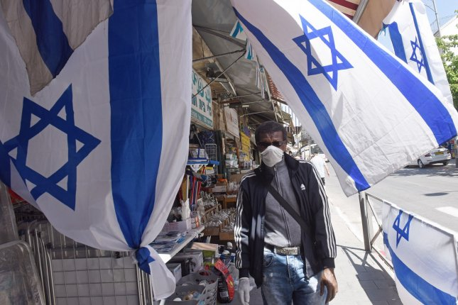 A man wears a face mask on Tuesday outside a shop displaying multiple Israeli flags to commemorate Memorial Day and Independence Day in Jerusalem. Photo by Debbie Hill/UPI