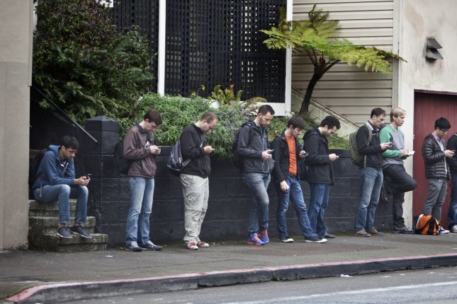 Tech workers check their phones as they wait for a bus to Silicon Valley. Google workers announced Monday a new global union alliance. File Photo by Terry Schmitt/UPI