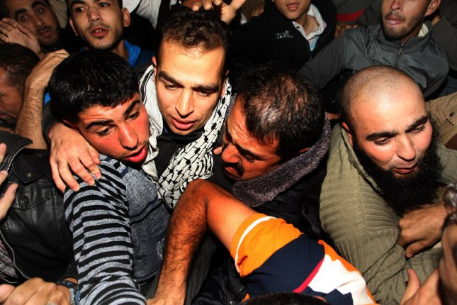 Released Palestinian prisoner Hazem Shbeir (C) is hugged by his relatives upon his arrival at his home in Khan Younis, southern Gaza, Oct. 30. Israel is due to release a third batch of prisoners next week despite recent terrorist attacks. UPI/Ismael Mohamad