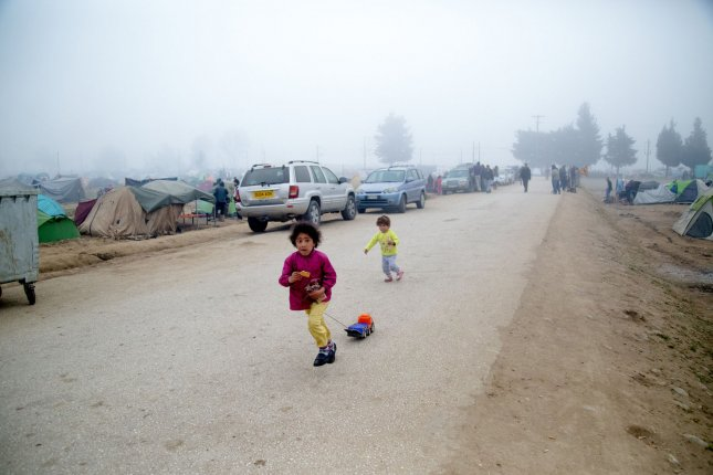 A pair of young migrant children are seen playing along a dirt road at a refugee camp in Greece. A UNICEF report says 50 million children have been displaced worldwide. Photo by David Caprara/UPI