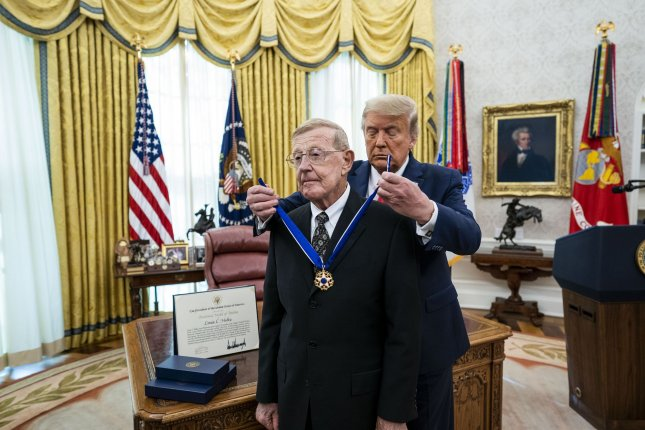 President Donald Trump (R) presents the Medal of Freedom to Lou Holtz in the Oval Office on Thursday at the White House in Washington, D.C. Pool photo by Doug Mills/UPI