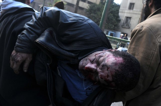 Egyptian protesters carry a wounded demonstrator following clashes with security forces near Cairo's Tahrir Square on December 17, 2011. UPI/Mohamad Hosam