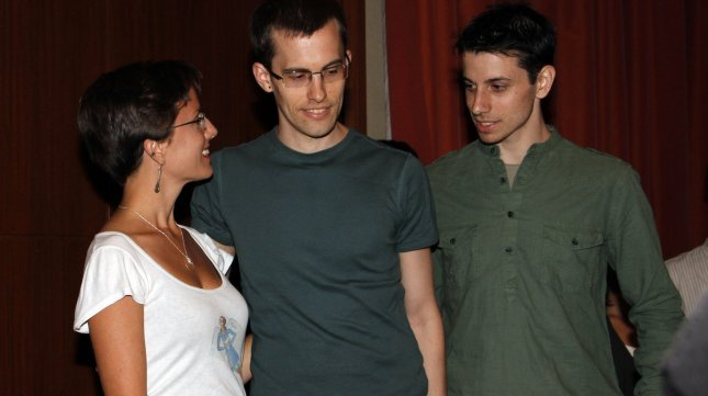 Josh Fattal (C) and Shane Bauer (R), the two American hikers who were released after being held in an Iranian prison for more than two years, embrace with Sarah Shourd following a press conference on their imprisonment at the Parker Meridien New York on September 25, 2011.UPI/Laura Cavanaugh