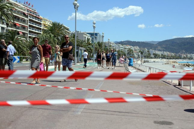 People walk along the Promenade des Anglais open to pedestrians in Nice, Southern France, on Sunday. Eighty-hour people were killed and hundreds more injured when a truck mowed down a crowd of revelers attending the Bastille Day fireworks. Photo by Maya Vidon-White/UPI