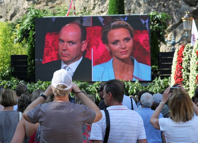 Monegasques, citizens of Monaco, crowd around a large video screen set up next to Saint Devote church to watch the civil wedding of Prince Albert II and Princess Charlene in Monte Carlo, Monaco on July 1, 2011. The Prince and Princess will complete their nuptials with a religious ceremony tomorrow. UPI/ David Silpa