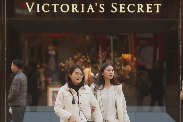 Chinese women walk past a massive Victoria's Secret boutique in Beijing in 2018. The lingerie chain's owner sold a majority stake in the company to a private equity firm on Thursday. File photo by Stephen Shaver/UPI