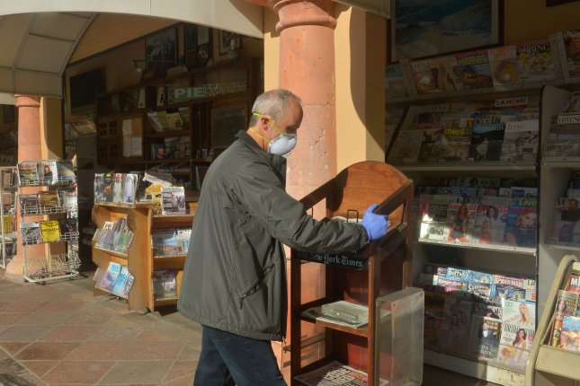A shopkeeper closes his magazine stand early in Malibu, Calif., on Monday. Governors and mayors across the country have implemented orders requiring residents to stay home and not gather in groups in order to contain and mitigate the coronavirus pandemic. Photo by Jim Ruymen/UPI
