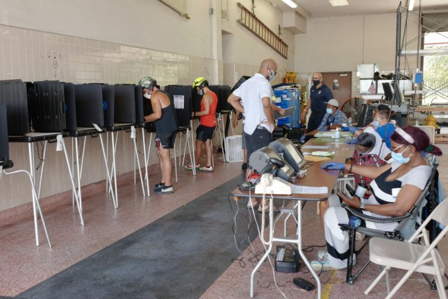 Miami residents check in at the registration desk and cast their ballot in the primary election August 18. On Friday, an appeals court said Florida ex-felons must pay all fines before registering to vote. File Photo by Gary I Rothstein/UPI