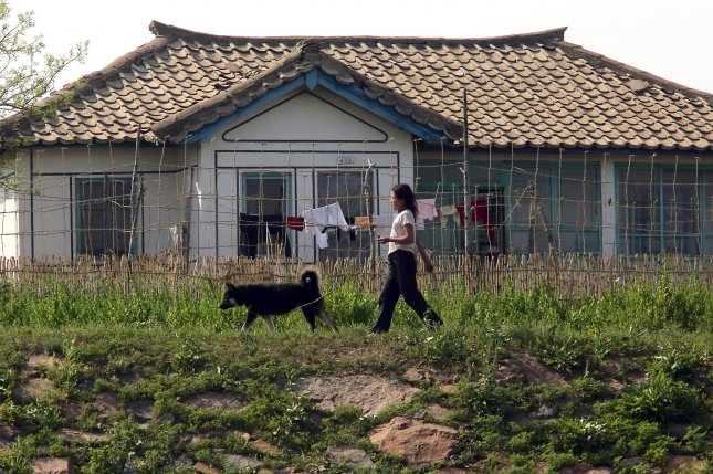 A North Korean woman walks her dog in a small village near the North Korean city Sinuiju, across the Yalu River from Dandong, China's largest border city with North Korea. Private ownership of land is being allowed in the country. File Photo by Stephen Shaver/UPI