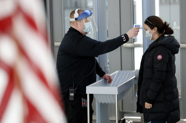 A security guard checks the temperature of a voter as she enters the building on Election Day at Rocket Mortgage Fieldhouse in Cleveland. Photo by Aaron Josefczyk/UPI