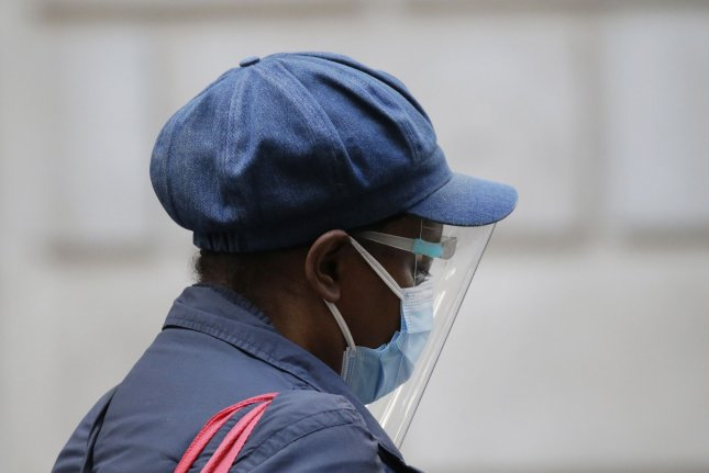 A pedestrian wears a mask and face shield while walking on Wall Street in New York City on Friday. Photo by John Angelillo/UPI