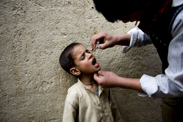 A health worker administers the polio vaccine to a child in Afghanistan. Wednesday, the Bill and Melinda Gates Foundation announced it would pay off a $76 million tab in Nigeria that the country used to eradicate polio. File Photo by Hossein Fatemi/UPI