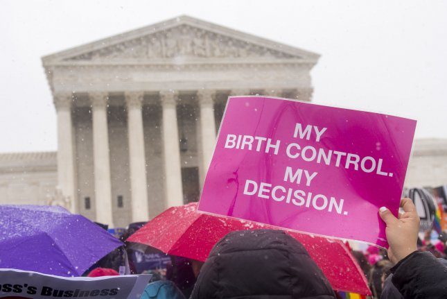 Women's rights supporters rally in front of the U.S. Supreme Court. A judge on Sunday blocked new rules that would've allowed employers in 13 states to stop covering birth control for employees. File Photo by Kevin Dietsch/UPI