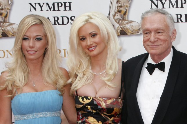 Kendra Wilkinson (L) with Holly Madison and Hugh Hefner (R) in June 2007. The reality star defended Hefner following Madison's tell-all memoir release this week. File photo by David Silpa/UPI
