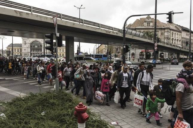 Syrian refugees walk toward the Kelenfšld train station in Budapest last September. Former militiamen accused of committing crimes during Syria's war are now blending in and seeking asylum in Europe. File Photo by Achilleas Zavallis/UPI
