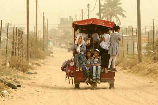A new study suggests extreme temperatures, drought and sandstorms could push millions in the Middle East and North Africa from their homes in the coming decades. Pictured, Palestinian school children ride a rickshaw in Khan Yunis in southern Gaza during a sandstorm that sent hundreds of people across the Middle East to hospitals with breathing difficulties, September 9, 2015. Photo by Ismael Mohamad/UPI