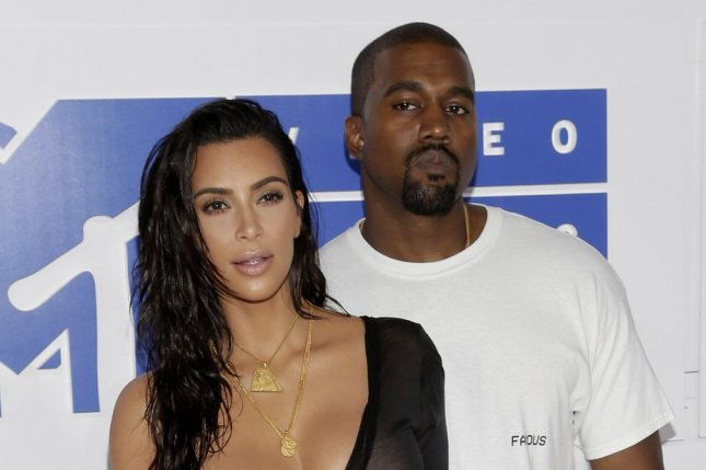 Kanye West (R) and Kim Kardashian at the MTV Video Music Awards on August 28. The rapper signed Tyga to his record label. File Photo by John Angelillo/UPI