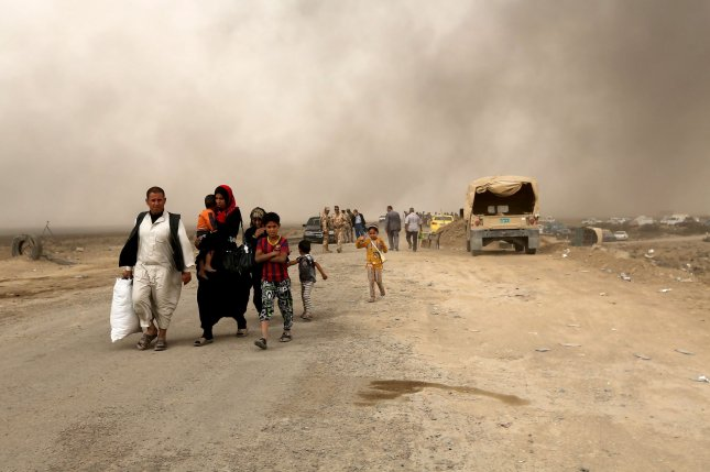 Iraqi civilians flee from fighting while smoke rises from the burning oil fields Qayara, Iraq, near Mosul, on November. 1. Friday a statement by the United Nations High Commissioner for Human Rights outlined atriocitries committed by the Islamic State within Mosul. Photo by Murat Bay/UPI