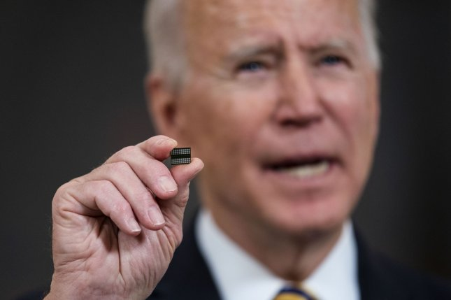 President Joe Biden holds up a semiconductor as he delivers remarks before signing an executive order on the economy on February 24. Pool Photo by Doug Mills/UPI