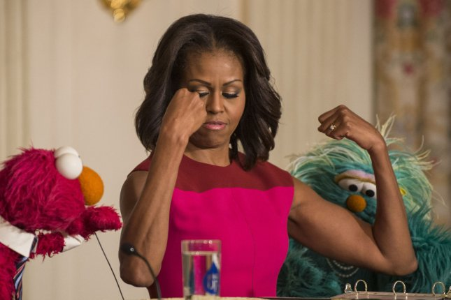 First Lady Michelle Obama shows her muscles to Sesame Street's to Elmo and Rosita during an an announcement to partner in a marketing campaign to help children eat healthier foods, at an event in the State Dining Room of the White House in Washington, DC on October 30, 2013. The trio later joined children in the annual fall harvest of the White House Kitchen Garden. UPI/Pat Benic