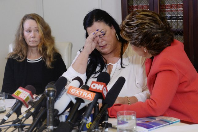 Pamela Abeyta reacts during a news conference with three new alleged sexual assault victims of comedian Bill Cosby while attorney Gloria Allred comforts her in Los Angeles on September 30, 2015. A new California law ending the statue of limitations to prosecute rape allegations will not help the women in the Cosby case because it applies to rapes and sexual assaults committed after the legislation takes effect Jan. 1. File photo by Jim Ruymen/UPI