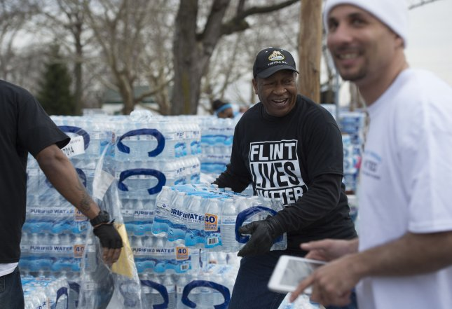 The Michigan state attorney general announced the first criminal charges in the polluting of Flint's water supply. Volunteers distribute cases of water at City Hall in Flint last month. Photo by Molly Riley/UPI