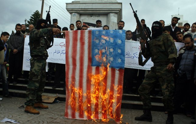 Members of the armed Palestinian group Popular Resistant Committees burn a US flag during a demonstration in support of Iraqi journalist Muntazer al-Zaidi, who threw shoes at US President George W. Bush in Iraq, in Gaza City on December 16, 2008.(UPI Photo/Ismael Mohamad)
