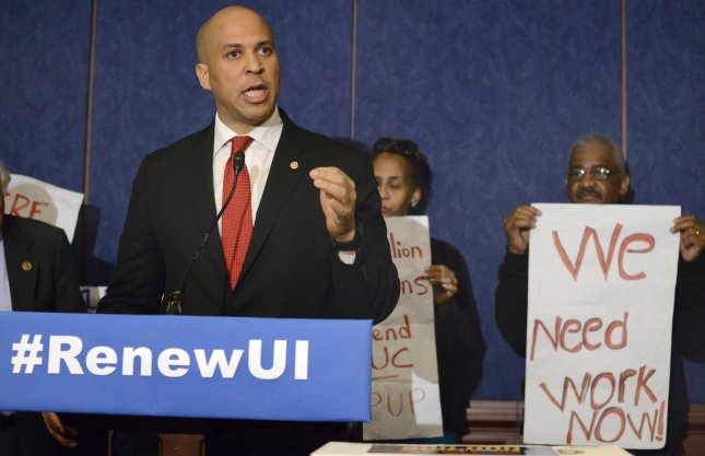 U.S. Sen. Cory Booker (D-NJ) makes remarks at a press briefing to rally support for Congress to renew unemployment insurance benefits, which earlier failed to pass Republican opposition, at the US Capitol, January 16, 2014, in Washington, D.C. Labor leaders hold signs to support jobless Americans. UPI/Mike Theiler