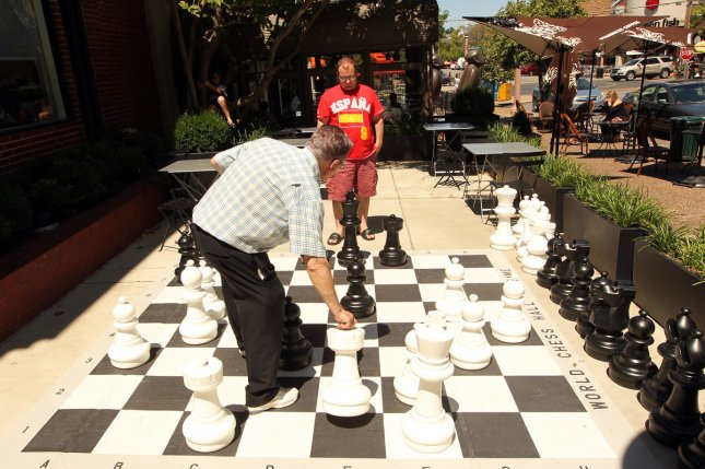 Visitors to the World Chess Hall of Fame play an interactive, oversized game of chess outdoors in St. Louis on June 22, 2012. (File/UPI/Bill Greenblatt)