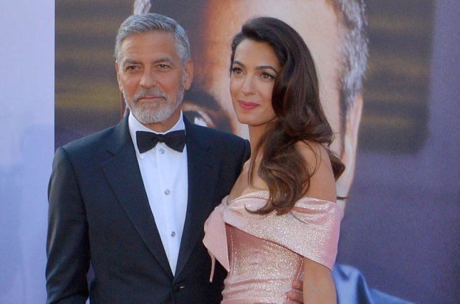 George Clooney (L) with his wife Amal Clooney. George was hit by a car while riding a scooter in Italy. File Photo by Jim Ruymen/UPI