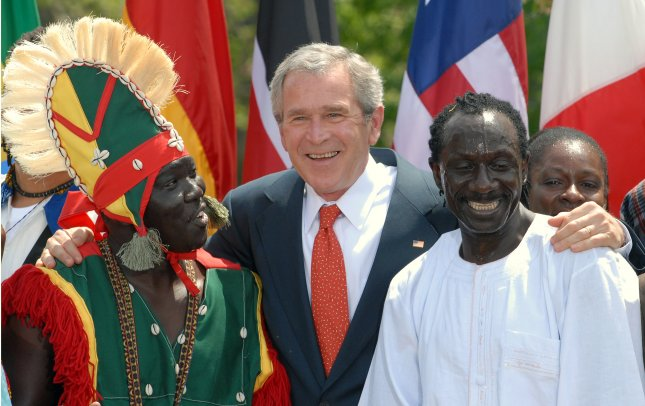 Former U.S. President George W. Bush posed with Medoun Yacine Gueye (L) and Assan Ronte during a performance by the Kankouran West African Dance Company during an event marking Malaria Awareness Day in the Rose Garden of the White House on April 25, 2007. (UPI Photo/Roger L. Wollenberg)