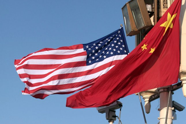 United States and Chinese flags fly over Tiananmen Square in Beijing. A Chinese negotiator said Tuesday the U.S. administration is holding a knife at the neck of Beijing in the ongoing trade conflict. File Photo by Stephen Shaver/UPI